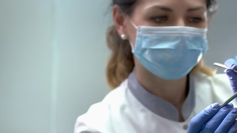 Female dentist in gloves working. Mouth mirror and probe. Dental insurance guide.