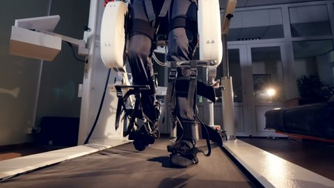 A man inside an exoskeleton walking a treadmill.