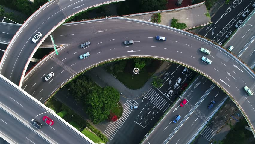 Rotating drone view into the center of busy multilevel interchange flyover in Shanghai showing afternoon traffic coming from the elevated roads