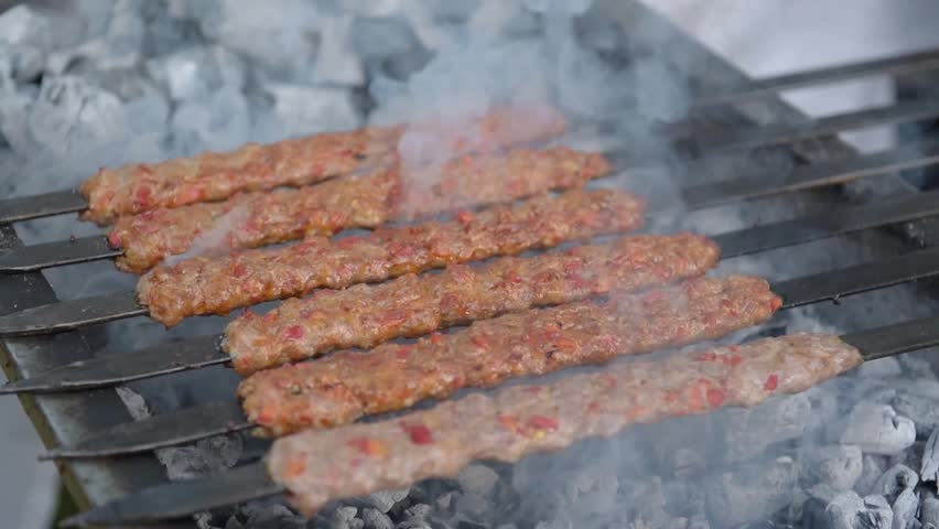 Several raw traditional Turkish shish Adana Kebab skewers that made of meat are lined up over charcoal in barbecue.