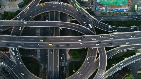 Aerial top down view on busy multilevel interchange overpass in Shanghai showing afternoon traffic coming from the elevated roads