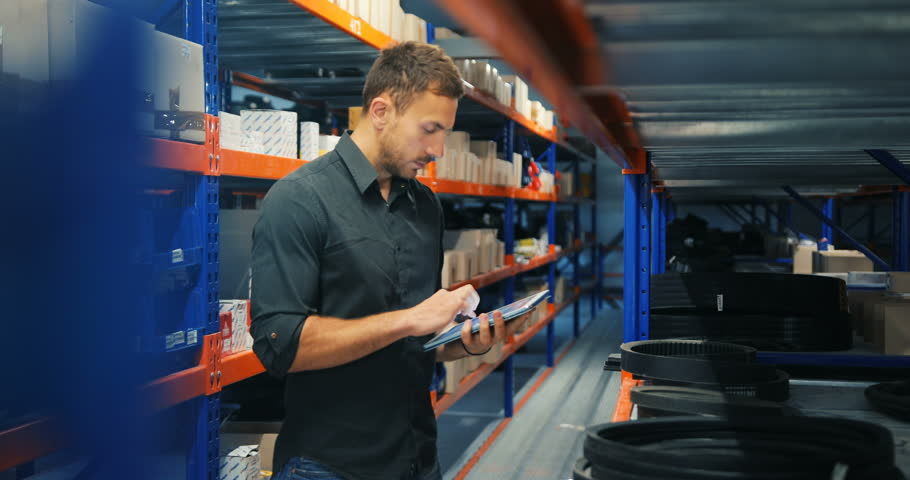 Man in a warehouse is checking inventory levels of goods, using his tablet, Last in last out, First in first out concept photo, orange-blue perspective background