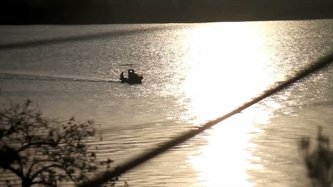 little fishing boat through dawning sun reflection