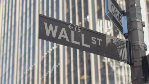 CLOSE UP: Street sign of iconic Wall Street, a collective name for the financial and investment community, stock exchanges, large banks, brokerages, securities, underwriting firms and big businesses