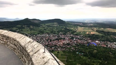 Arial view of Stuttgart, Esslingen and surrounding cities as seen from castle Hohenneuffen in Southern Germany with a paraglider