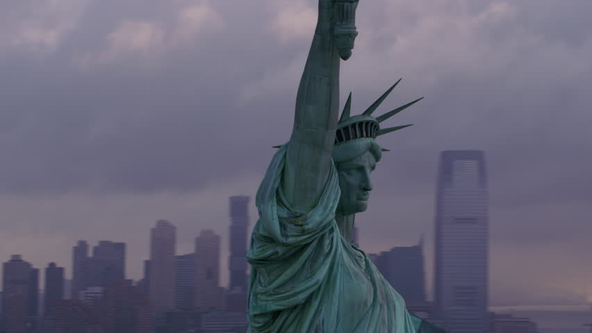New York City circa-2017, Pull out from close-up of Statue of Liberty to reveal Manhattan and morning clouds. Shot with Cineflex and RED Epic-W Helium. | Shutterstock HD Video #28499761