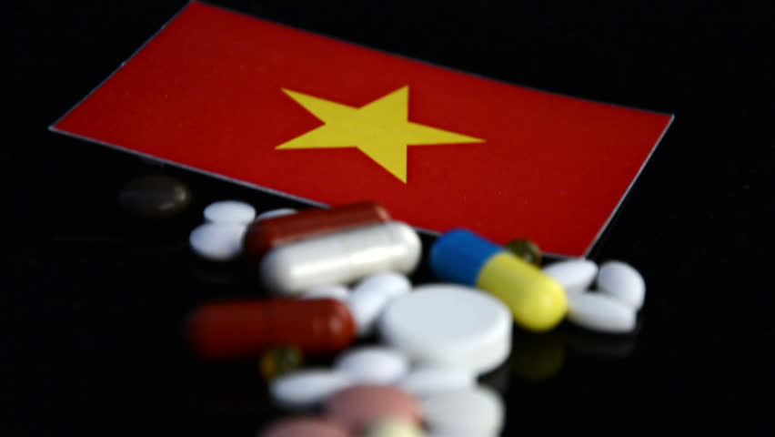 Vietnamese flag with lot of medical pills isolated on black background | Shutterstock HD Video #28525531