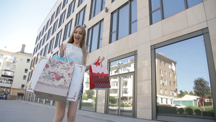 Young blonde girl along the shop windows, happy shopping | Shutterstock HD Video #28533511