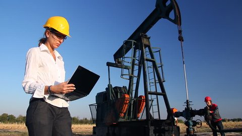 Female engineer and oil man working together in an oilfield, teamwork