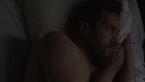 Lonely sad man with insomnia lying in his bed and thinking about problems