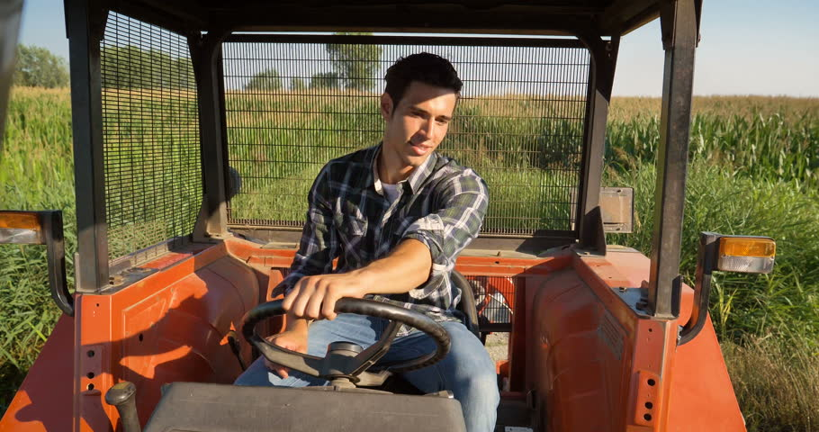 Portrait of a beautiful young farmer (student), sits inside in the tractor cabin, rides the field, turns the steering wheel, happy in a shirt, cornfield. Concept ecology, transport, farmers, clean air