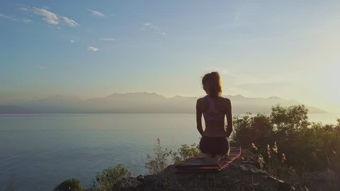backside view slim girl with ponytail sits in yoga pose on steep cliff against sunrise above ocean
