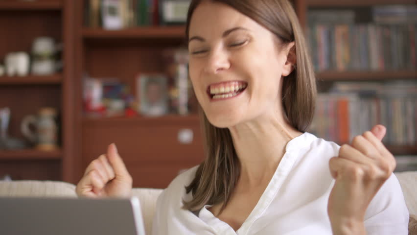 Young successful businesswoman using laptop at home living room home office, professional female employer receiving good news excited happy cheerful smiling. Success and achievement concept