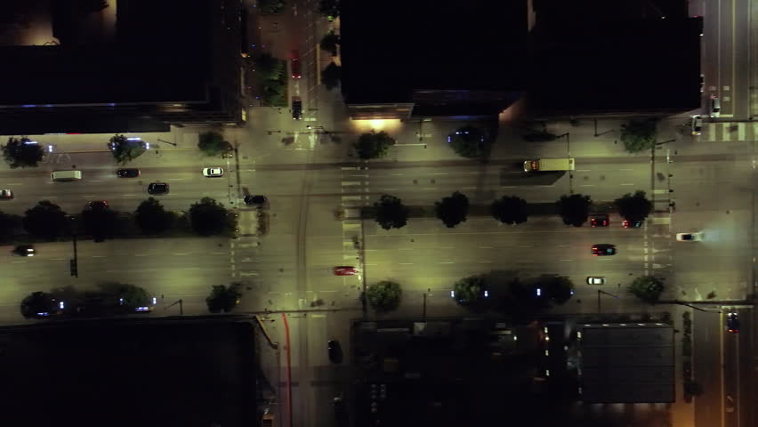 Overhead Aerial of Cars Driving by City Blocks at Night Passing Intersection