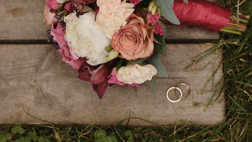 Wedding rings and wedding bouquet at wooden and grass surface | Shutterstock HD Video #28600552