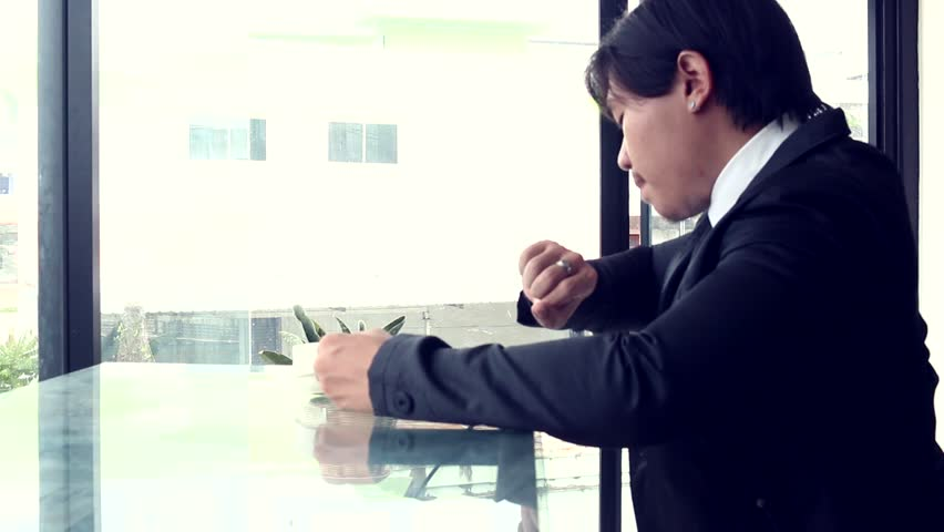 Man in a suit looks out the window then drinks from a cup | Shutterstock HD Video #28604149