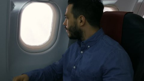 On a Transatlantic Flight Young Hispanic Male Opens Shade and Looks out of the Window. Shot on RED EPIC-W 8K Helium Cinema Camera.