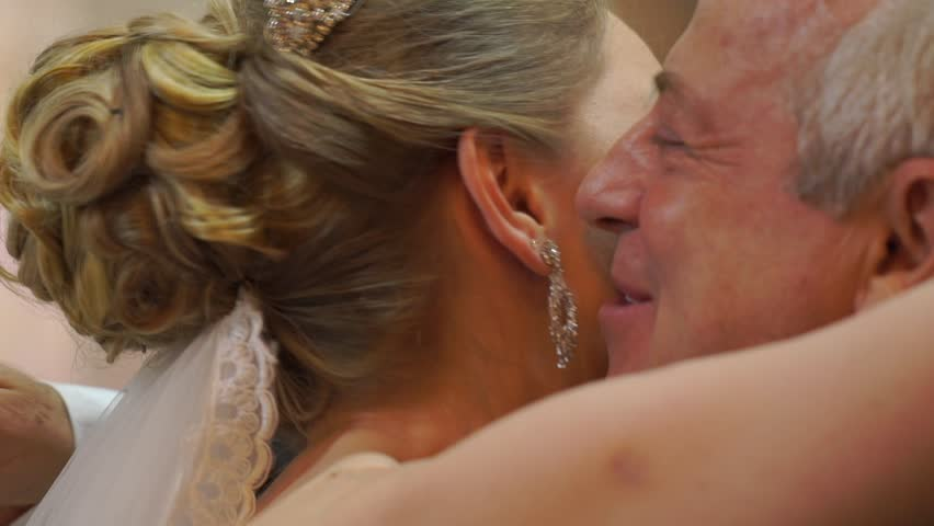 Bride and fathering-law embrace at exciting moment at church ceremony