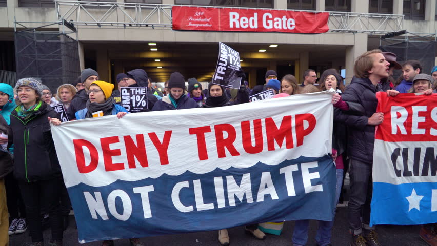 Washington D.C.-2010s: Protestors hold up signs saying DENY TRUMP NOT CLIMATE during an anti-Trump rally in Washington DC.
