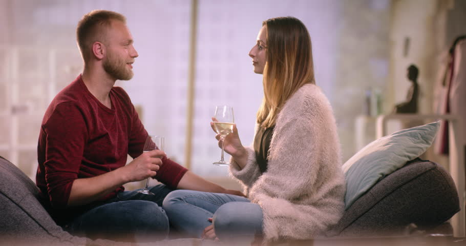 Happy couple sitting crossed-legs on couch and clincking glasses | Shutterstock HD Video #28633717