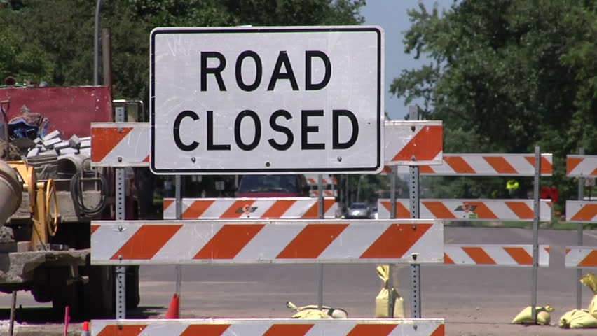 """Two shots of same scene (one medium, one wide) showing a road closed due to construction. Features """"Road closed"""" signs."""