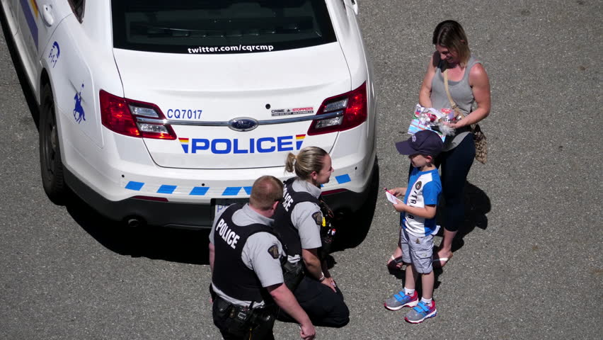 Coquitlam, BC, Canada - June 26, 2017 : Top shot of police officer hugging with children beside police car with 4k resolution