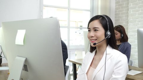 Asian business team working in call center as the operators (or telemarketers)