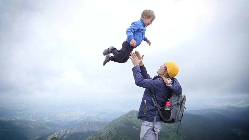 Young Father Playfully Throw Up In Air And Catch Little Child Son On Nature Hiking Walking Tatras Mountains