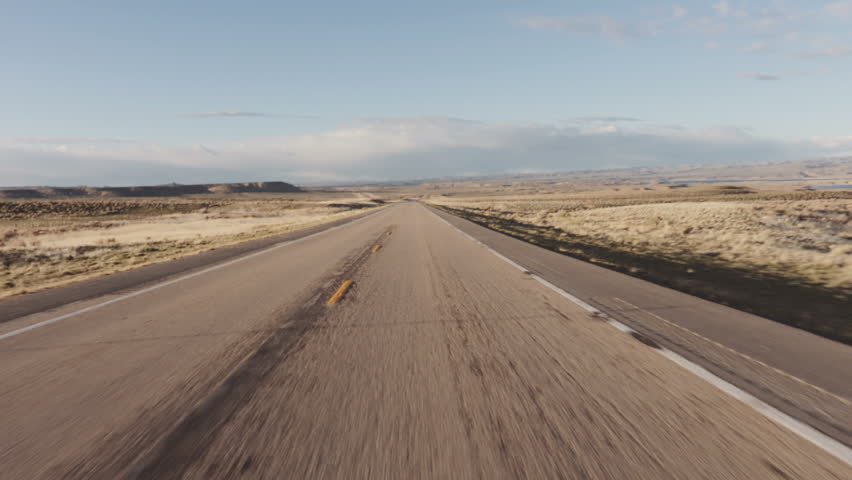 Driving USA: The open road – beautiful point of view shot driving on long straight road in desert grasslands at sunrise/sunset, Wyoming | Shutterstock HD Video #28662841