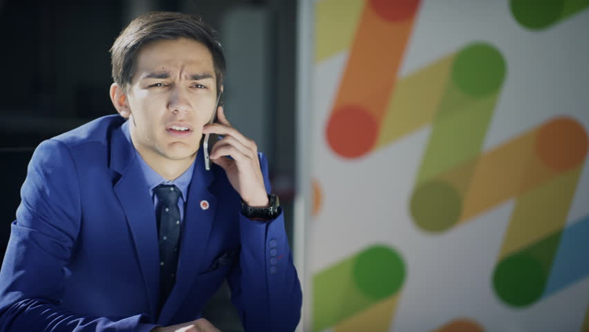 A man in a business suit is talking on the phone reluctantly. A man in blue attire sits at a table and communicates with a partner about an unpleasant problem. The male figure holds a pencil in his