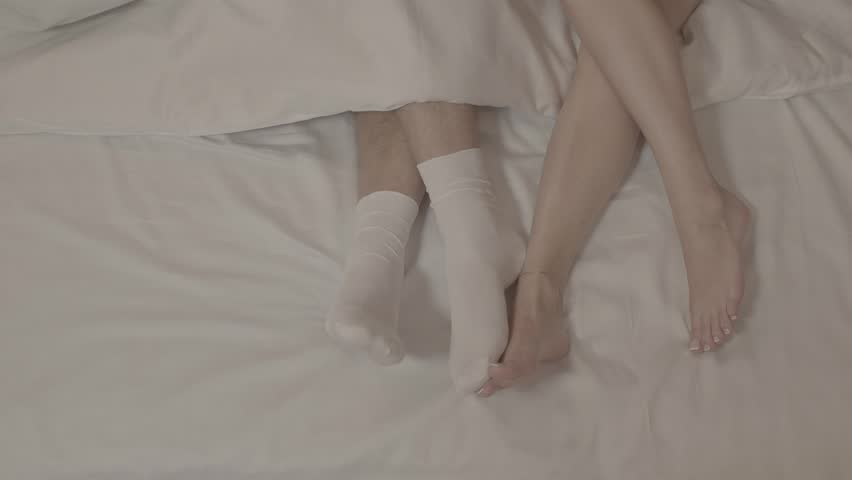 Two women with bare feet laying on bed touching man legs in white socks under blanket on white bed sheets in close up