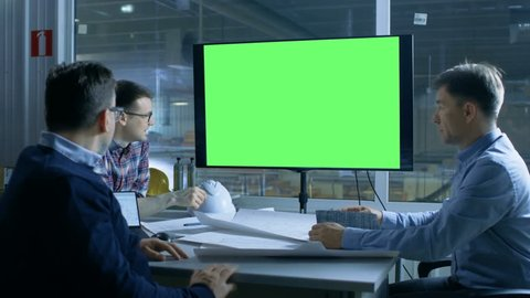 Team of Industrial Engineers Have Important Meeting. Presentation Display Shows Mock-up Green Screen. In the Background Factory is Seen. Shot on RED EPIC-W 8K Helium Cinema Camera.