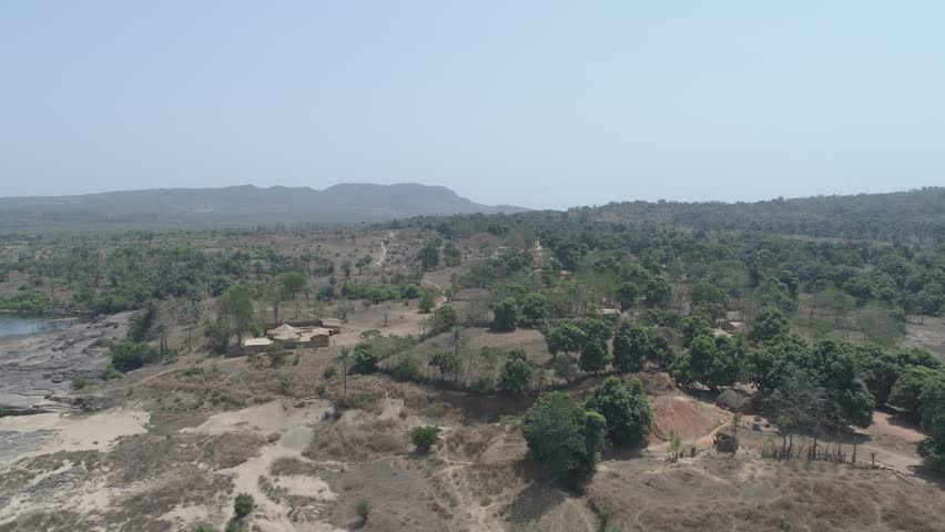 Aerial view over the landscape of Guinea, drone view with blue sky over trees and little huts in West Africa