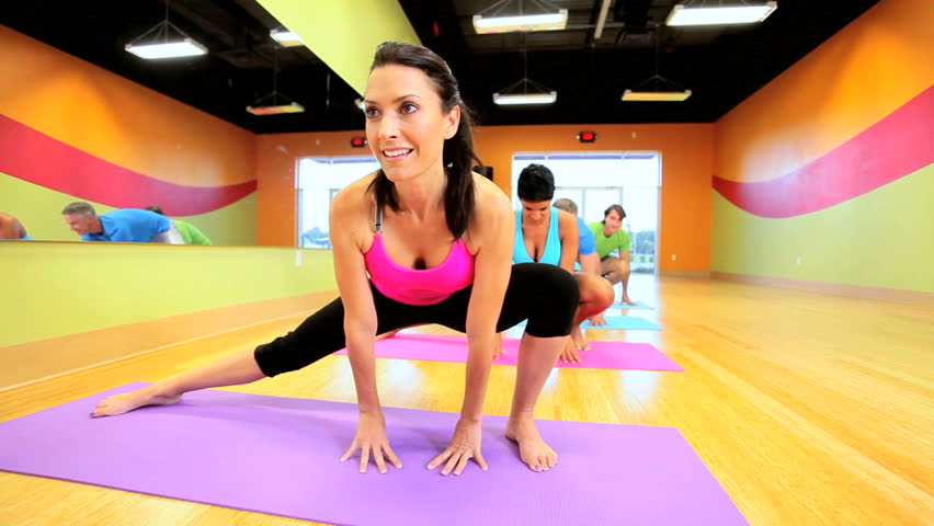 Caucasian female fitness instructor with multi ethnic class using mats for floor exercises