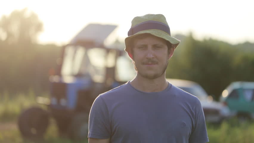 Portrait of young farmer in hat standing at field of organic farm with the tractor on the background. Man looking at camera and smiling in beautiful sunset light. #28703551
