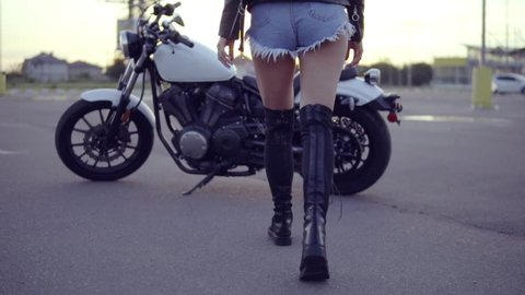 Back view of a female biker in shorts coming up and getting on the motorcycle. Young sexy curly woman in sunglasses on the chopper