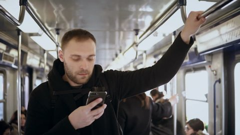 Young handsome man uses the smartphone in public transportation, in metro. Male surfing the Internet with touchscreen