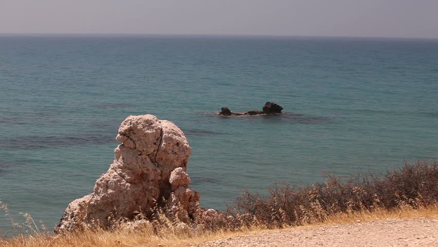 Rocks stick out of the sea water, rocky beach high cliffs blue sky and sea, Sea coast with rocks, Rock sticking vertically out of the water, Greece, Cyprus, the pool of Aphrodite