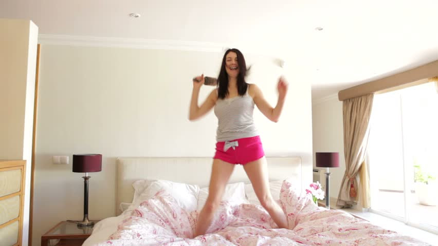 """Woman jumping on bed singing into hairbrush """"microphone"""". 