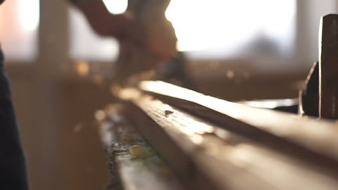 A man sawing wood Board with hand saw. Closeup. Slow motion