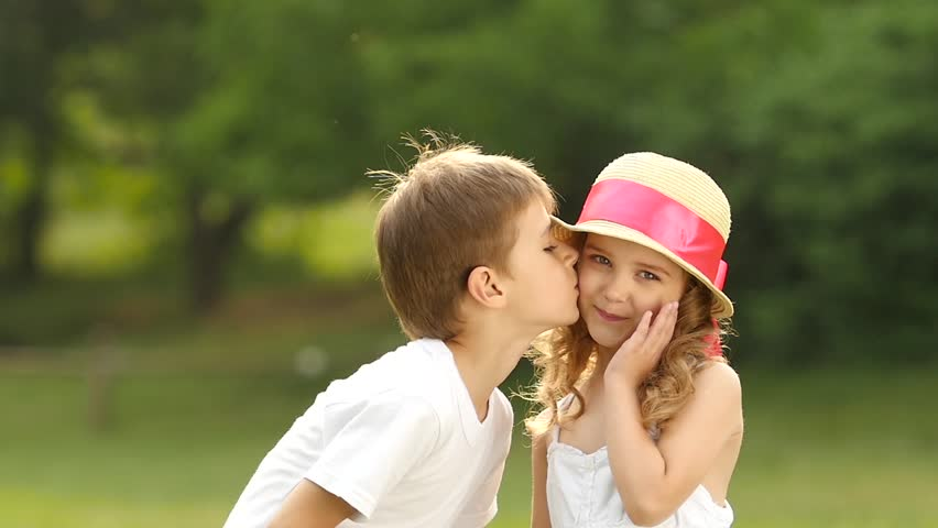 Little boy kisses the girl on the cheek she is embarrassed and little boy kisses the girl on the cheek she is embarrassed and smiles slow altavistaventures Images