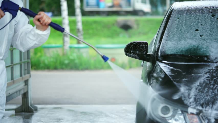 Young caucasian man washing foam off his car. Car washing self-service. Water spray with hig pressure cleaner