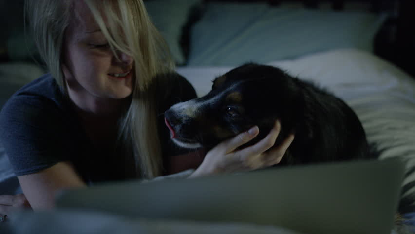 Woman getting licked by dog in bed | Shutterstock HD Video #28750051
