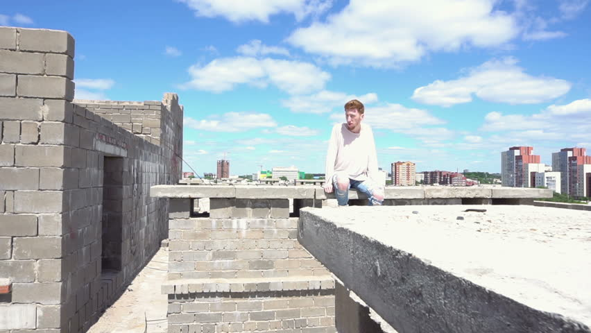 Young redhead man in a white sweatshirt sits on a brick wall on the roof | Shutterstock HD Video #28753141