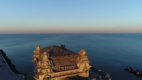 Aerial footage of a waterfront with a castle at sunset.