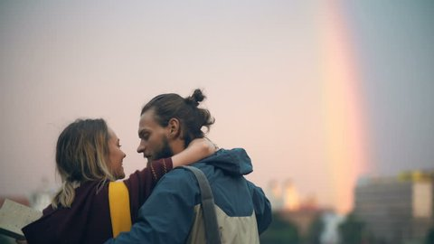 Romantic date of young couple in the city centre on sunset. Happy man and woman hug, kiss, enjoying the time together.
