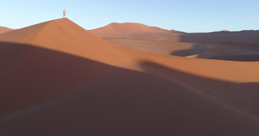 Tilt up aerial view of male tourist taking walking down one of the vast sand dunes in the Namib desert | Shutterstock HD Video #28779601