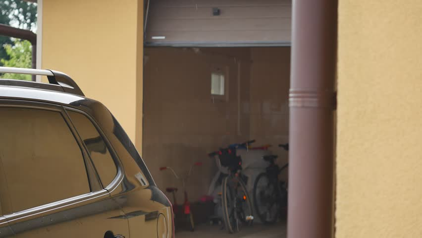 Man driver in car thumbed remote control to open the garage door.
