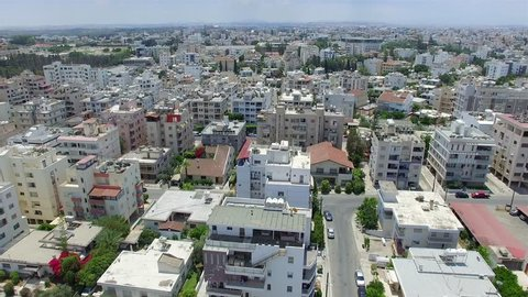 Aerial left moving tracking shot while gaining altitude within the buildings of the Acropolis area in Nicosia, Cyprus.