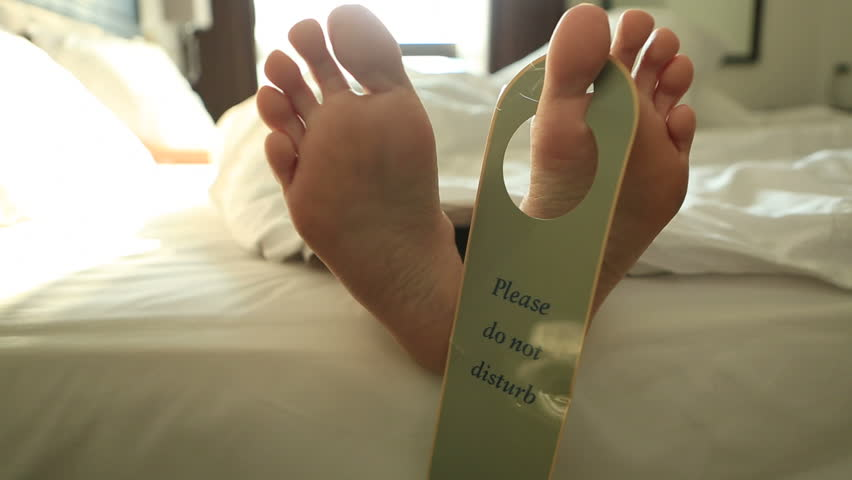 Human's feet on bed with 'do not disturb' sign Happy feet of a person laying down in a comfortable bed in an hotel room with the sign 'do not disturb' hanging on them. | Shutterstock HD Video #28801891
